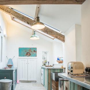 Cette image montre une buanderie parallèle chalet de taille moyenne avec un placard, un évier de ferme, un plan de travail en zinc, un mur blanc, un sol en calcaire, des machines côte à côte et un sol gris.