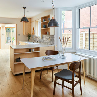 Photo of a modern utility room in London with open cabinets, light wood cabinets, solid surface benchtops, medium hardwood floors, a concealed washer and dryer, brown floor and yellow benchtop.