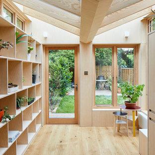 Idéer för ett modernt gul grovkök, med öppna hyllor, skåp i ljust trä, bänkskiva i koppar, mellanmörkt trägolv, tvättmaskin och torktumlare byggt in i ett skåp och brunt golv