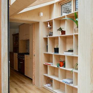 Идея дизайна: универсальная комната в стиле модернизм с открытыми фасадами, светлыми деревянными фасадами, столешницей из акрилового камня, паркетным полом среднего тона, со скрытой стиральной машиной, коричневым полом и желтой столешницей