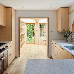 Foto på ett funkis gul grovkök, med öppna hyllor, skåp i ljust trä, bänkskiva i koppar, mellanmörkt trägolv, tvättmaskin och torktumlare byggt in i ett skåp och brunt golv