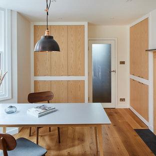 Exemple d'une buanderie moderne multi-usage avec un placard sans porte, des portes de placard en bois clair, un plan de travail en surface solide, un sol en bois brun, des machines dissimulées, un sol marron et un plan de travail jaune.