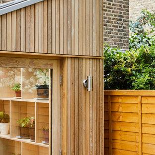 Idéer för funkis gult grovkök, med öppna hyllor, skåp i ljust trä, bänkskiva i koppar, mellanmörkt trägolv, tvättmaskin och torktumlare byggt in i ett skåp och brunt golv
