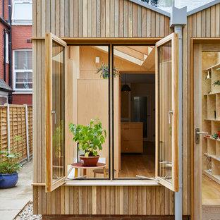 Inspiration pour une buanderie minimaliste multi-usage avec un placard sans porte, des portes de placard en bois clair, un plan de travail en surface solide, un sol en bois brun, des machines dissimulées, un sol marron et un plan de travail jaune.