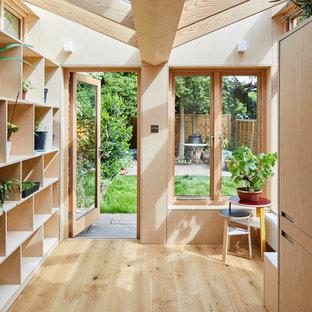 На фото: универсальная комната в стиле модернизм с открытыми фасадами, светлыми деревянными фасадами, столешницей из акрилового камня, паркетным полом среднего тона, со скрытой стиральной машиной, коричневым полом и желтой столешницей