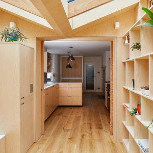 Пример оригинального дизайна: универсальная комната в стиле модернизм с открытыми фасадами, светлыми деревянными фасадами, столешницей из акрилового камня, паркетным полом среднего тона, со скрытой стиральной машиной, коричневым полом и желтой столешницей