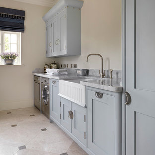 Design ideas for a traditional single-wall separated utility room in Other with limestone flooring, a belfast sink, shaker cabinets, blue cabinets, beige walls, a side by side washer and dryer and grey floors.