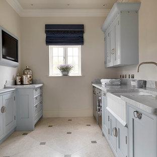 Ispirazione per una lavanderia tradizionale con pavimento in pietra calcarea e pareti grigie