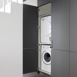 Photo of a contemporary laundry cupboard in London with flat-panel cabinets, grey cabinets, a stacked washer and dryer, grey floors and concrete flooring.