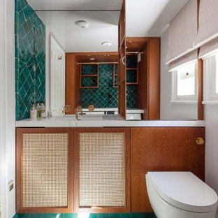 Small midcentury utility room in London with an integrated sink, quartzite benchtops, white walls, marble floors, a concealed washer and dryer, green floor and white benchtop.