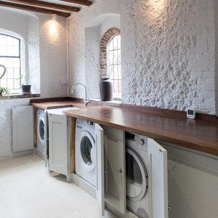 Inspiration för lantliga brunt tvättstugor enbart för tvätt, med en rustik diskho, skåp i shakerstil, grå skåp, träbänkskiva, vita väggar och tvättmaskin och torktumlare byggt in i ett skåp