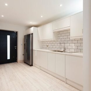 Large modern single-wall utility room in Kent with a double-bowl sink, flat-panel cabinets, white cabinets, quartz worktops, white walls, vinyl flooring and a concealed washer and dryer.