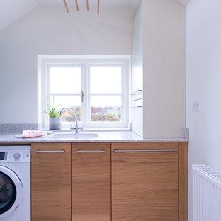 Exempel på en mellanstor modern u-formad tvättstuga, med släta luckor, skåp i mellenmörkt trä, grått stänkskydd, glaspanel som stänkskydd, kalkstensgolv och en undermonterad diskho