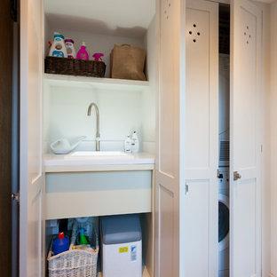 Idee per un piccolo ripostiglio-lavanderia country con lavello da incasso, ante grigie, top in quarzite, pareti bianche, pavimento in pietra calcarea e lavatrice e asciugatrice a colonna