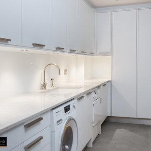 Cette photo montre une buanderie tendance avec des portes de placard blanches, un plan de travail en quartz, une crédence en dalle de pierre et un sol en carrelage de porcelaine.