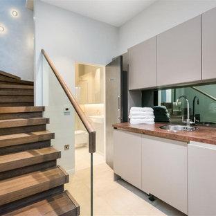 Свежая идея для дизайна: маленькая прямая универсальная комната в современном стиле с одинарной раковиной, плоскими фасадами, бежевыми фасадами, деревянной столешницей, зеркальным фартуком, полом из керамогранита и со скрытой стиральной машиной - отличное фото интерьера