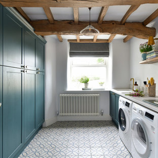 Inspiration for a country galley laundry room in Other with an undermount sink, shaker cabinets, turquoise cabinets, white walls, a side-by-side washer and dryer, multi-coloured floor, grey benchtop and exposed beam.