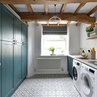 Immagine di una lavanderia country con lavello sottopiano, ante in stile shaker, ante turchesi, pareti bianche, lavatrice e asciugatrice affiancate, pavimento multicolore, top grigio e travi a vista