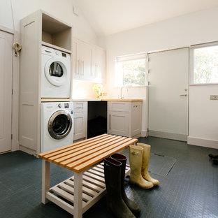 Inredning av en klassisk beige l-formad beige tvättstuga, med en tvättpelare, skåp i shakerstil, vita skåp, träbänkskiva, vita väggar och linoleumgolv