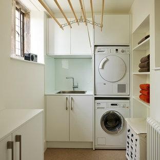 Modern inredning av ett mellanstort u-format grovkök, med en integrerad diskho, släta luckor, vita skåp, laminatbänkskiva, vita väggar, klinkergolv i porslin och en tvättpelare