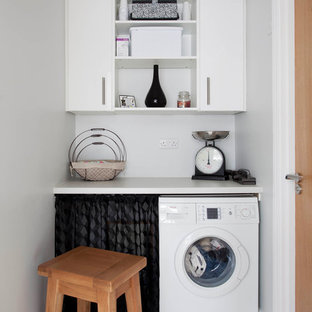 Inspiration for a small transitional laundry room in Dublin with multi-coloured splashback, stone slab splashback, ceramic floors, open cabinets, white cabinets and white walls.