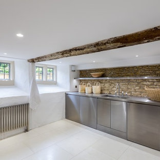 Inspiration for a contemporary laundry room in Gloucestershire with stainless steel cabinets, stainless steel benchtops and limestone floors.