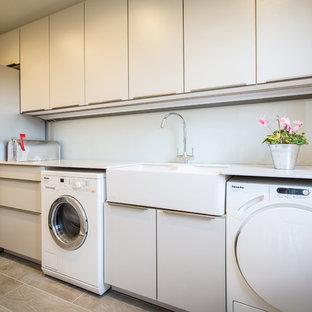 Inspiration för små moderna linjära tvättstugor enbart för tvätt, med grå skåp, stänkskydd med metallisk yta, spegel som stänkskydd, en rustik diskho, släta luckor, bänkskiva i koppar, vita väggar och en tvättmaskin och torktumlare bredvid varandra