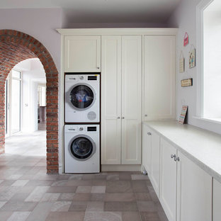 Medium sized classic l-shaped utility room in Dublin with shaker cabinets, white worktops, beige cabinets, grey walls, a stacked washer and dryer and grey floors.