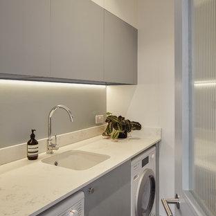 Modelo de cuarto de lavado lineal, nórdico, con fregadero bajoencimera, armarios con paneles lisos, puertas de armario grises, paredes blancas, lavadora y secadora juntas, suelo gris y encimeras blancas