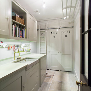 Inspiration for a large traditional separated utility room in London with a belfast sink, shaker cabinets, white cabinets, white walls and a concealed washer and dryer.