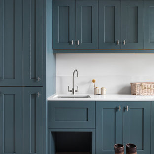 Photo of a mid-sized traditional galley utility room in Other with an integrated sink, shaker cabinets, blue cabinets, quartzite benchtops, white splashback, stone slab splashback, vinyl floors, grey floor, white benchtop, white walls and an integrated washer and dryer.