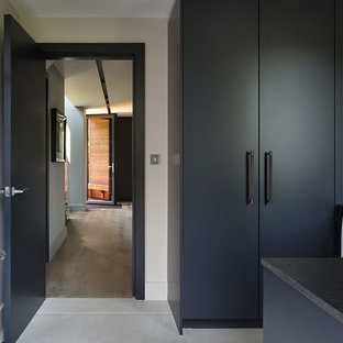 Large contemporary single-wall utility room in London with a submerged sink, marble worktops, light hardwood flooring, flat-panel cabinets, grey cabinets, grey walls, an integrated washer and dryer and black worktops.