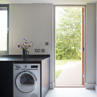 Inspiration for a large contemporary single-wall utility room in London with a submerged sink, marble worktops, light hardwood flooring, flat-panel cabinets, grey cabinets, grey walls, an integrated washer and dryer and black worktops.