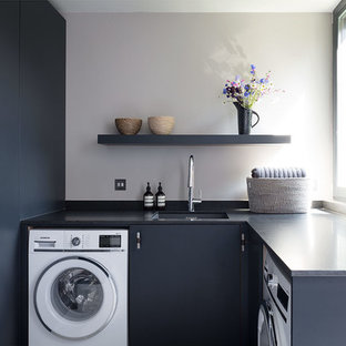 This is an example of a small contemporary u-shaped utility room in London with a submerged sink, marble worktops, light hardwood flooring, flat-panel cabinets, black cabinets, grey walls, black worktops and an integrated washer and dryer.