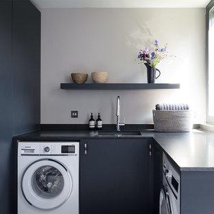 Foto di una piccola lavanderia contemporanea con lavello sottopiano, top in marmo, parquet chiaro, ante lisce, ante nere, pareti grigie, top nero e lavasciuga