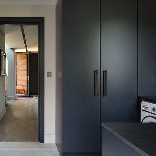 This is an example of a large contemporary single-wall utility room in London with a submerged sink, marble worktops, light hardwood flooring, grey cabinets, flat-panel cabinets, grey walls, an integrated washer and dryer and black worktops.