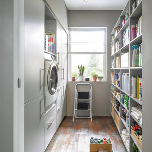 Design ideas for a contemporary galley utility room in Other with flat-panel cabinets, white cabinets, white walls and grey floors.