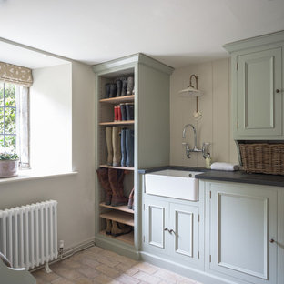 Inspiration for a large cottage galley brick floor and beige floor laundry room remodel in Dorset with a farmhouse sink, recessed-panel cabinets, gray cabinets, granite countertops, beige walls and black countertops