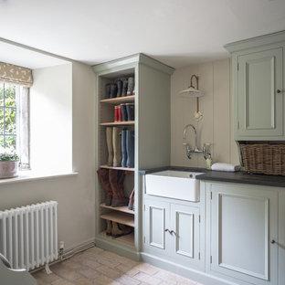 Exempel på en stor lantlig svarta parallell svart tvättstuga, med en rustik diskho, luckor med infälld panel, grå skåp, granitbänkskiva, beige väggar, tegelgolv och beiget golv
