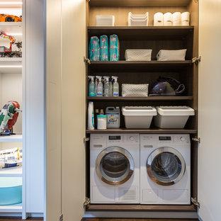Foto på ett litet funkis brun linjärt grovkök, med släta luckor, grå skåp, träbänkskiva, vita väggar, mörkt trägolv, tvättmaskin och torktumlare byggt in i ett skåp och brunt golv