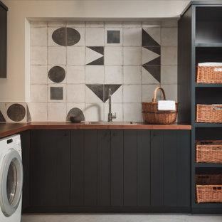 Lantlig inredning av en bruna l-formad brunt tvättstuga enbart för tvätt, med en nedsänkt diskho, släta luckor, svarta skåp, träbänkskiva, grå väggar, en tvättmaskin och torktumlare bredvid varandra och grått golv