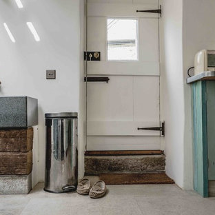 Cette image montre une buanderie chalet en L multi-usage et de taille moyenne avec un évier utilitaire, un placard avec porte à panneau encastré, des portes de placard en bois vieilli, un plan de travail en zinc, un mur blanc, un sol en calcaire, des machines côte à côte et un sol beige.