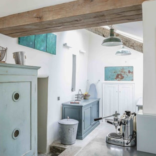 Inspiration for a mid-sized shabby-chic style l-shaped limestone floor and beige floor utility room remodel in Devon with recessed-panel cabinets, distressed cabinets, white walls and a side-by-side washer/dryer