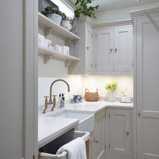Photo of a mid-sized traditional l-shaped laundry room in London with a farmhouse sink, shaker cabinets, quartzite benchtops, white splashback, subway tile splashback, light hardwood floors, beige cabinets, beige floor and white benchtop.