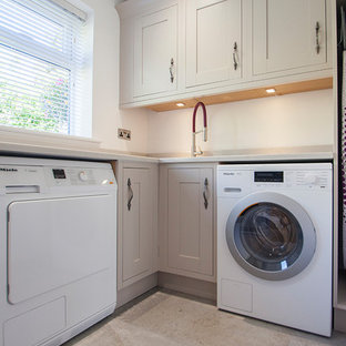 Design ideas for a large transitional u-shaped laundry room in Wiltshire with grey cabinets, quartzite benchtops, stone slab splashback, light hardwood floors and brown floor.