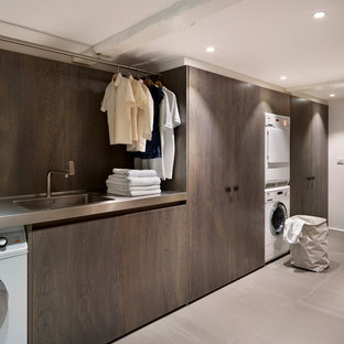 Cette image montre une buanderie design dédiée avec un évier intégré, des machines superposées, un plan de travail en inox et un plan de travail gris.