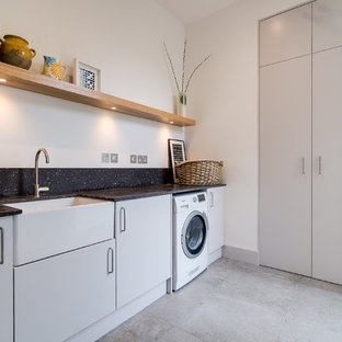 Photo of a medium sized contemporary single-wall utility room in London with a belfast sink, flat-panel cabinets, grey cabinets, granite worktops, white walls, ceramic flooring, grey floors and black worktops.