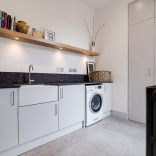 Design ideas for a medium sized contemporary single-wall laundry cupboard in London with a belfast sink, flat-panel cabinets, grey cabinets, granite worktops, white walls, ceramic flooring, grey floors and black worktops.