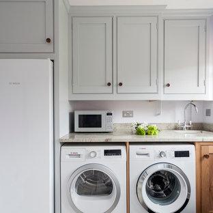 Esempio di una piccola lavanderia tradizionale con ante a filo, top in granito, lavello sottopiano, ante grigie, pareti viola e lavatrice e asciugatrice affiancate
