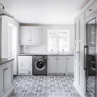 Inredning av ett modernt mycket stort grå u-format grått grovkök, med en enkel diskho, skåp i shakerstil, grå skåp, laminatbänkskiva, grå väggar, klinkergolv i keramik, en tvättmaskin och torktumlare bredvid varandra och gult golv